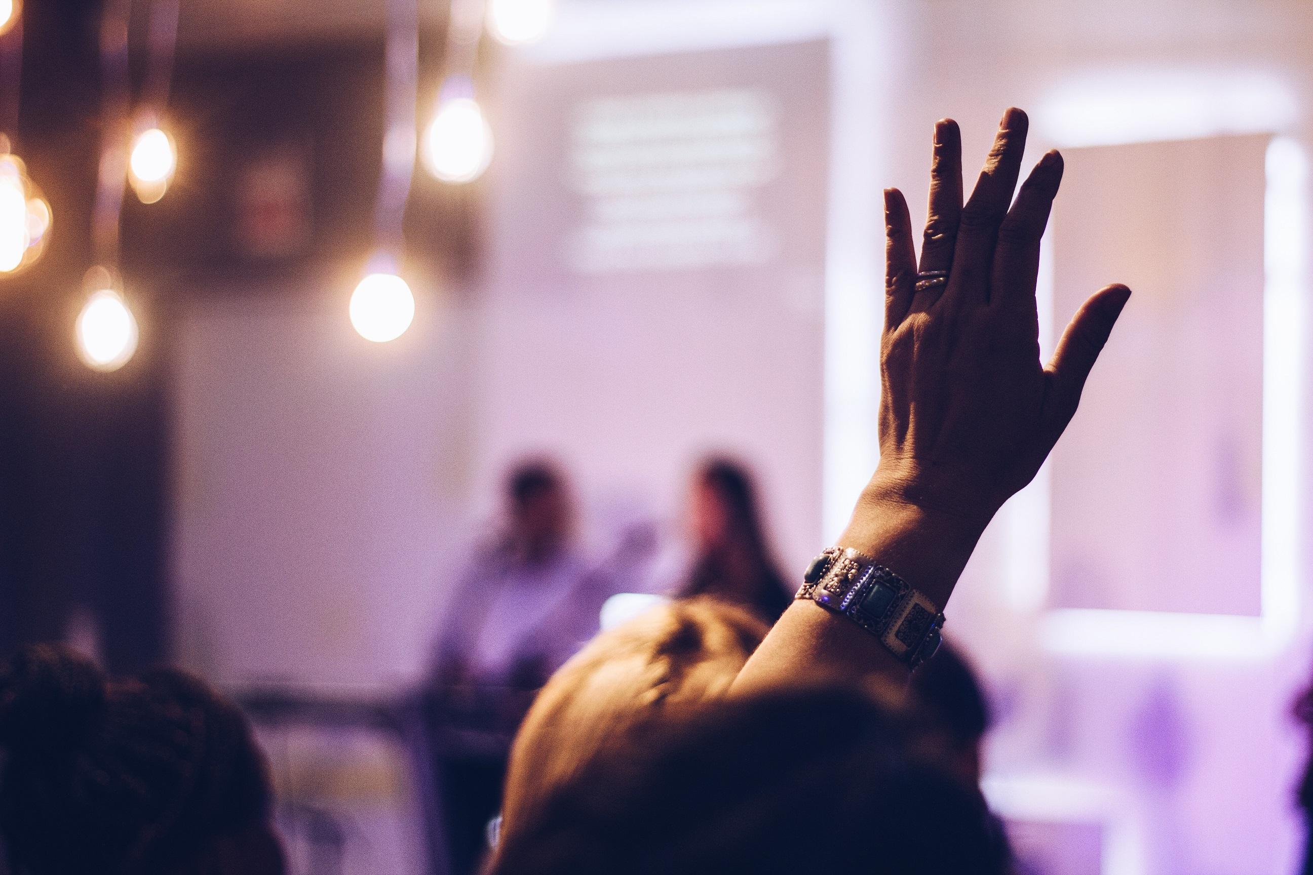 Medarbetare räcker upp handen och är delaktig på konferens